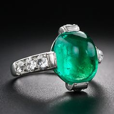 A gorgeous, bright crystalline green, high-domed (or sugarloaf) cabochon emerald, weighing about 5.00 carats, glistens and glows atop an elegantly handcrafted platinum and diamond solitaire style mounting, dating from the heyday of Art Deco splendor - circa 1930. Each shoulder of the ring sparkles with a trio of high-crowned old mine-cut diamonds
