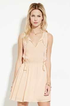 A sleeveless woven dress with eyelet embroidery framing the armholes, a tasseled self-tie split neckline, and an elasticized waist.
