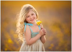 Adorable little girl with blonde hair and a tan and blue dress poses for outdoor portraits in a field of yellow wildflowers near Las Vegas. LJHolloway Photography is a Las Vegas Children