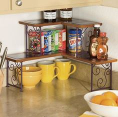 """Colorblock 2-Tier Corner Shelf takes a bold approach to kitchen organizing. Give your work area a burst of color—while you create more convenient spots for towels, soap, lotion, scrubbies, spices, cookbooks—whatever you need to keep close at hand. Non-warping composite wood tiles brighten their scrolled wrought iron bases. Easy two-step assembly. 2-Tier Corner Shelf is 18"""" l x 14"""" h x 18"""" d (assembled), with 5 3/4"""" w shelves."""