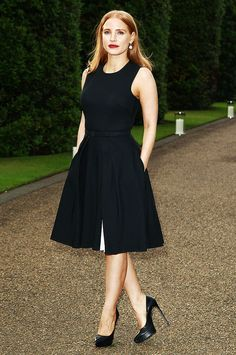 Jessica Chastain wears a black knee-length dress with black pumps and statement earrings