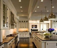 traditional beautiful white kitchen with dark hardwood floors black soapstone counter silver pendant lights