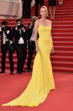 Charlize Theron on the Cannes Film Festival red carpet wearing a yellow gown by Dior is one of the prettiest film festival dresses of all time.