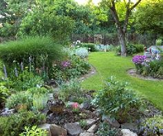 The irregular curves give the garden a soft, welcoming feel -- as do plants such as the ornamental grass and fluffy pink heads of phlox.