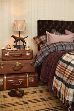 Great masculine bedroom with vintage suitcases, various plaids and brown velvet tufted headboard.