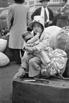 An American child and her doll waiting for a train to forcibly transport her and her family to a World War II internment camp for Japanese immigrants and Americans of Japanese descent, Owens Valley, California, United States, 1942, photograph by Russell Lee.