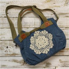 Our adorable denim handbag is ready for duty. Durable denim canvas soft side bag. Trimmed with a crochet large ecru doily. Fully lined with a zippered pouch and 2 media pouches. The antique side rings