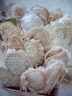 Cut various size heart patterns out and make them up in ivory, white pr beige. Then use ivory or white lace over the base and put flowers on them. Buttons and ribbon, too. Lace may be over a pale pink satin, too. On some of them, the lace looks like t