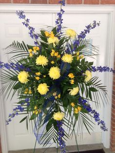 Fresh spray with blue delphinium, yellow mums and yellow roses  (School colors)