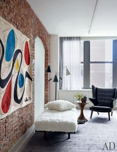At the other end of the space, a 1970s weaving modeled after the work of Alexander Calder brightens a brick wall; Henderson designed the shearling-covered daybed.
