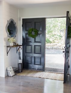 Stunning entryway - love the black front door and the planked wall eclecticallyvintage.com