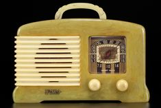 "<span style=""text-decoration: underline;""></span>FADA SW-57/L-56 in onyx with alabaster wrap-around grill, knobs + handle. This Art Deco catalin model made in 1939 by FADA Radio + Electric Company has a beautiful design and size. The SW-57 version of the L-56 style is the shortwave model with a switch on the back. The chassis in this model is bigger going all the way to the back edge; this made it that Fada had to add two factory holes on the bottom rear edge to secure the larger chassis…"