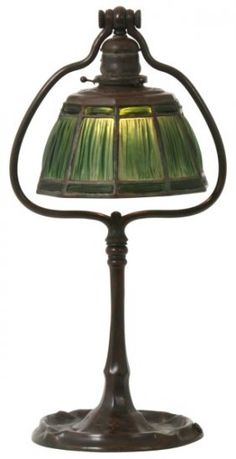 "Tiffany Studios Linenfold Harp Desk Lamp. 10 sided shade with 3 rows of green linenfold ""Favrile Fabrique"" glass and a red-brown patina, signed ""Tiffany Studios, 1938""; in excellent condition with no chipped or cracked panels, 8 in. dia. On a bronze desk lamp harp base with single socket hanging from the top cluster, has a ruffled platform base; signed ""Tiffany Studios New York, 590"", in excellent condition. 19.25 in. high."