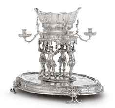 A Baroque-style Silver Figural Epergne and Plateau, German or Austrian,  circa 1870  shaped oval plateau chased with running bellflowers and strapwork, the surface with four classical profiles, on wood base with parquetry starburst; four warrior figures supporting the central pierced oval basket, scroll branches topped by warriors