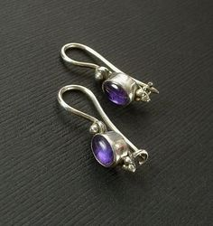 An Enchanting Pair of Vintage Sterling Silver Amethyst Earrings bezel-set with Natural Amethyst Cabochon Gemstones in a Sterling Silver Byzantine Setting, Tested and Hallmarked 925 for Sterling Silver, Locking French Earwires for Pierced Ears, Weight 2.6 Grams circa 1980s!  Approx. Measurements are 1 in length from top to bottom by 3/16 in width. Excellent condition!  These Sterling Silver Earrings have Genuine Polished Amethysts! They have a Deep Purple color with an Intense Vibrant Gl...