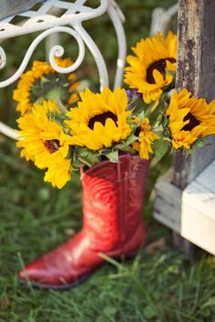 Country charm ~ What's not to like? Red boot, yellow sunflowers, green grass an old wood, white metal furnitiure????