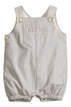 NEWBORN EXCLUSIVE/CONSCIOUS. Macacão forrado em tecido de algodão orgânico com pernas curtas com elástico. Tem alças com botão e um pequeno bolso no peito,