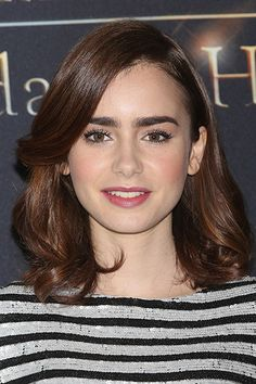 The Best Brown Hair Colors That Are Anything But Mousy - Her pretty pink blush isn't the only thing that's giving Lily Collins' skin a glow. With just the slightest hint of red tones, her warm brown hair color enlivens her fair complexion.