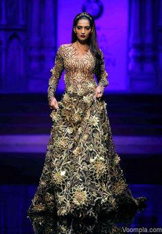 Sonam Kapoor walks the ramp for Abu Jani Sandeep Khosla in a black multi-panelled flared gown embellished with Swarovski crystals. via Voompla.com