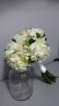 White wedding bouquet. Hydrangeas, peonies, roses, freesia, mini spray roses, lisianthus, hypericum berries, dahlias, variegated pittosporum, ruscus leaves, garden roses, baby's breath.