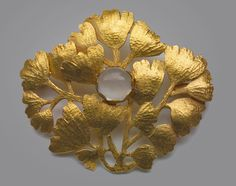 JULES DAUVERGNE (Worked from c.1900-c.1925) Japonisme Maidenhair Brooch. Gold, Moonstone. France, c. 1910. Maker's mark: ' J Sword Dauvergne D' .  The golden Maidenhair fern in this impressive & beautiful brooch has the refreshing naturalism that Japonisme introduced to Western jewelry of this period. Literature: cf. Art Nouveau Jewelry, Joseph Sataloff, 1984, p. 92  (hva)