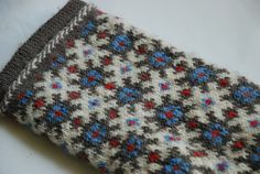 This Latvian mitten pattern comes from the district of Ventspils and features a cuff with a scalloped edge. The model mitten was knit in brown, green, yellow, red, and white.