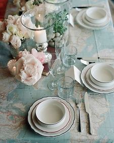 A fabric depicting a map of the world in a slightly desaturated palette was used as a table cloth, and succulents, roses, and peonies decorated the table. Photo by Elizabeth Messina