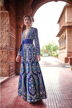 A glorious blue floor length jacket with full length sleeves and pockets on both the sides is exquisitely embroidered with gota patti, zardosi, dori, pearl and sequin work in motifs of trees branching out into rustling leaves and blossoming flowers inspired by the Bishnoi community's spiritual reverence for nature; cinched with an obi belt and layered with a champagne tulle gown. Arista jacket by Anita dongre