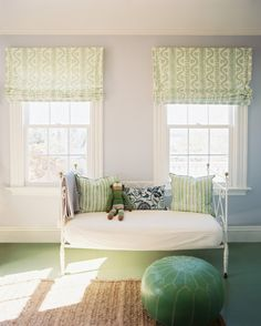 green pouf and a daybed in a room with patterned roman shades