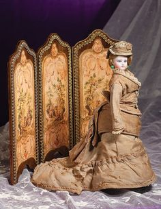 Doll wearing two-piece tan cotton gown with bustle and train, matching bonnet, original petticoat and brown leather boots. Ca 1875