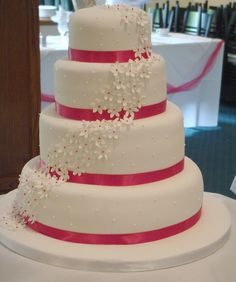 Four Tier Wedding Cake with Sugar Flower Daisies Cascading from Top Tier to Base Board - Hot Pink Ribbon and Matching Daisy Centres by handmadebyhannah, via Flickr