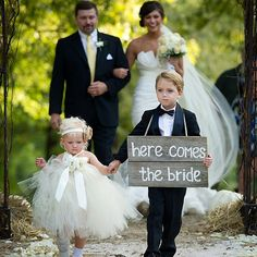 """LITTLE GIRL'S DRESS. """"Here Comes the Bride"""" signs are still going strong! Add a personalized touch with a funny message (""""Wait 'til you see her"""") or secret catchphrase you and your groom use (""""Love you to the moon and back"""").Photo Credit: Jason Crader"""