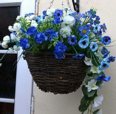 Pretty basket made of twigs and artificial plants in different shades of blue with white flowers and green foliage - very pretty artificial hanging basket