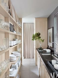 The working pantry, lined with open shelves for tableware, has a Kohler sink and fittings | archdigest.com