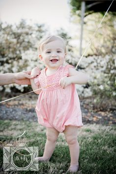 Little girl standing holding onto moms thumb and balloon string at her 1 year old session at Baxter Gardens by Knoxville Wedding Photographer, Amanda May Photos.