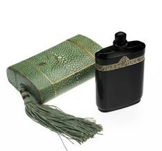 """A Monroe-owned perfume bottle housed in a green case. Nuit de Noel perfume by Caron in a vintage opaque black glass bottle with decorative gold foil label and a faceted stopper. In the original faux shagreen cardboard case with attached silk tassel. The box is marked inside the lid """"Caron 10 rue de la Paix Paris France."""" The case can be seen in a 1952 photograph taken of Monroe in her home. The bottle was given to Frank Rosenberg and his wife by Marilyn Monroe."""