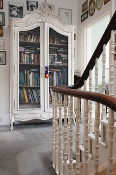Stairway landing with antique white armoire packed with books.