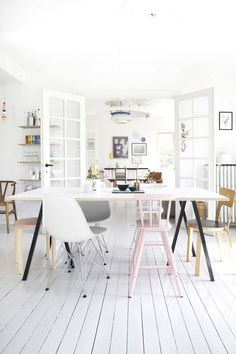 Danish style: white floors, walls and most of the furniture with some slashes of pastel colour. Open shelves (String?) and a couple of different design pieces.