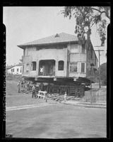 "House being moved from Colton and N. Boylston Sts. for construction of Hollywood Freeway, Calif., 1948. Caption when published in newspaper: ""Many are the structures being moved or razed to make way for freeway. Family still lives in this house being moved at Colton and N. Boylston Sts"" - Los Angeles Times Photographic Archive. Department of Special Collections, Charles E. Young Research Library, UCLA"
