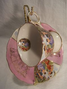 Offered is a Royal Halsey very Fine Bone China teacup and saucer with a bright brass wire twist holder. Both cup and saucer are bottom stamped in Gold---L (Crown Mark) M--Royal Halsey--Very Fine. The Cup & Saucer feature medallions of Greek Mythology type figures in a pastoral setting with an observant cherub. The saucer is 5 3/4 inches across and the cup is 2 3/4 inches tall. All are in excellent condition.