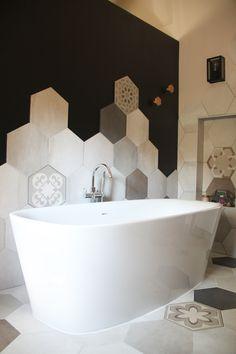 salle de bain avec une belle baignoire ilot et des faiences en carreaux ciment disposées de manière aléatoire ! Les patères rappellent la forme hexagonale. Une niche permet de disposer de la déco à côté de la douche !