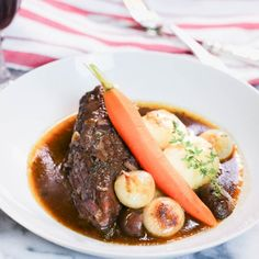 Coq au Vin, a classic French fricassée of chicken, slowly braised in mushrooms, onions, pork fat, Armagnac, and red wine.