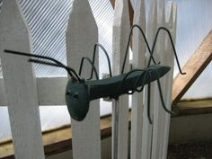 Cute grasshopper made using railroad spike and coat hanger wire.