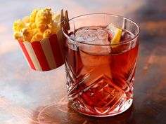 """Silver Screen: made from a popcorn-infused bourbon, cherry """"bespoke-a-cola"""" (cola reduction with cherry syrup) and a blend of bitters. Served with tiny popcorn bucket on the side."""