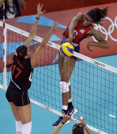 United States' Foluke Akinradewo, right, spikes the ball past Turkey's Neslihan Darnel during a women's preliminary volleyball match at the 2012 Summer Olympics, Sunday, Aug. 5, 2012, in London. (AP Photo/Jeff Roberson) (Associated Press) / SA