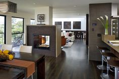 Smart design created a fireplace that serves three separate spaces:  kitchen, living area and dining room.