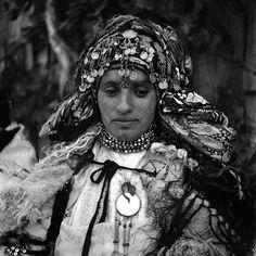 - Besancenot Jean (1902-1992) Portrait d'une femme des Aït Mguild avec sa coiffure de fête. Il s'agit de faire du volume ; plusieurs foulards sont superposés sur lesquels repose un lourd foulard de soie autour duquel s'enroulent deux diadèmes à pièces d'argent. En sautoir, elle porte un petit miroir et des colliers aux nombreux rangs. Elle a sur le visage les tatouages classiques de la tribu, et les pommettes frottées de blanc farineux.- Arago