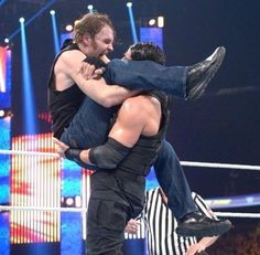 Roman Reigns touching and holding Dean Ambrose up by the bum