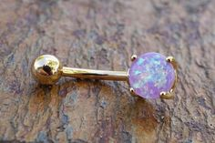 "Synthetic purple fire opal gold belly button jewelry ring. The 8mm purple opal is prong set and glows in the light with radiant iridescence. The opal gold belly ring is 14 gauge and 3/8"" long (10mm),"