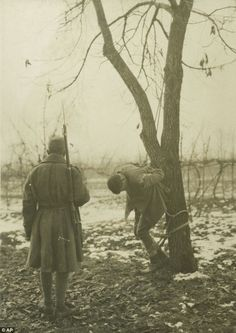 """In this 1917 photo, an Italian soldier stands in front of an executed soldier during the First World War in Italy. """